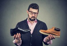 Young man making a shoe choice. Young perplexed beard man making a shoe choice having doubts royalty free stock photo