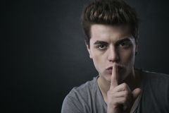 Young man making silence gesture Stock Photos
