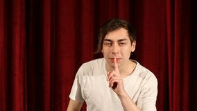 Young man making silence gesture, on red curtain background.  stock footage
