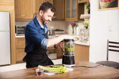 Young man making a smoothie Stock Photos