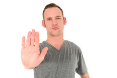 Young man making a Stop gesture. Holding up the flat of his palm with a determined expression on his face isolated on white Stock Images