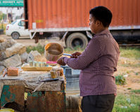 A young man making a tea. Shopkeeper pouring the prepared tea into the glass. He is an entrepreneur and runs the small tea stall near national highway 71. He is