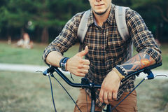 Young Man Is Making Thumb Up By Hands Sitting On A Bicycle On Green Summer Meadow Stock Photo
