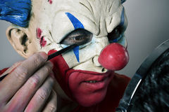 Young man making up himself as an evil clown Royalty Free Stock Photography