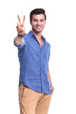 Young man making the victory peace sign Royalty Free Stock Photos