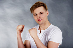 Young man making a wish. Young handsome hopeful man making fists Royalty Free Stock Image