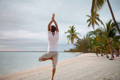 Young man making yoga exercises outdoors Stock Images