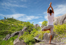 Young man making yoga tree pose outdoors Royalty Free Stock Photo