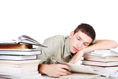 Young man with many books siting and writing Stock Images