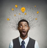 Young man with many idea light bulbs above head looking up. Isolated on gray wall background Stock Photos