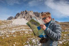 Young man with map in italien dolomites, loving nature and climbing, tre cime di lavaredo Stock Photo