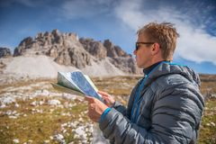 Young man with map in italien dolomites, loving nature and climbing, tre cime di lavaredo Stock Images