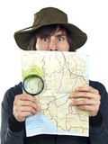 Young man with a map and magnifying glass Royalty Free Stock Photo