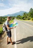 Young man with map on the road Stock Photo