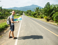 Young man with map on the road Stock Photography