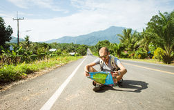 Young man with map on the road Royalty Free Stock Image
