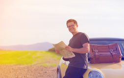 Young man with map standing near a car. At countryside Stock Photos