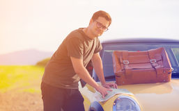 Young man with map and travel suitcase. Standing near a car at countryside Stock Photography