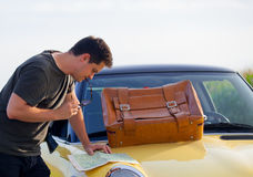 Young man with map and travel suitcase. Standing near a car at countryside Royalty Free Stock Photos