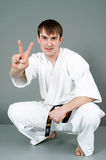 Young man in martial art suit. With black belt making victory sign with fingers, studio background Royalty Free Stock Photography
