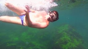 Young Man In Mask And Flippers Diving In The Sea. This is an underwater shoot of a young man in mask and flippers diving in the light blue waters of the sea stock video footage