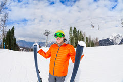 Young man in mask holds ski during mountain trip Royalty Free Stock Photo