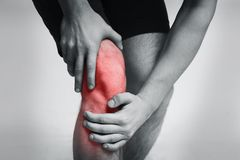 Young man massaging her painful knee closeup. Young man massaging his painful knee, black and white photo with red zone indicating trauma stock photos