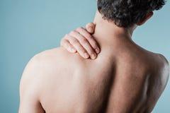 Young man massaging his sore neck Stock Photos
