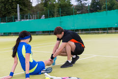 Young man massaging woman`s injured leg. Young men massaging woman`s injured leg after  tennis match on a court outdoor in summer or spring Royalty Free Stock Photography