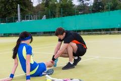 Young man massaging woman`s injured leg Royalty Free Stock Photography