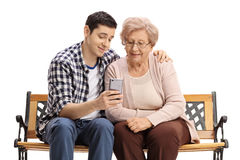 Young man with mature woman showing her something on phone. Young men sitting on a bench with a mature women and showing her something on a phone isolated on Royalty Free Stock Photos