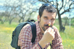 Young Man in a Meadow Smelling Flowers. Young Bearded Man on a Field Trip in Nature enjoying a Smell of Flowers Royalty Free Stock Images