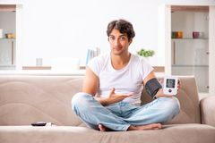 The young man measuring blood pressure at home. Young man measuring blood pressure at home stock photos