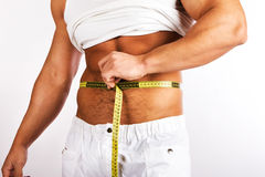 Young man measuring his waist Stock Photography