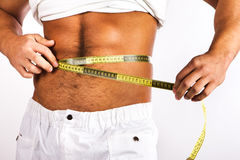 Young man measuring his waist Stock Photo