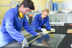 Young man measuring pane glass. Young men measuring pane of glass royalty free stock image