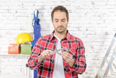 Young man measuring screw using caliper Stock Image