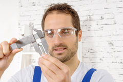 Young man measuring screw using caliper Royalty Free Stock Photography