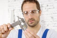 Young man measuring screw using caliper Royalty Free Stock Image