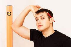 Young man with measuring tool and red pencil Stock Photos