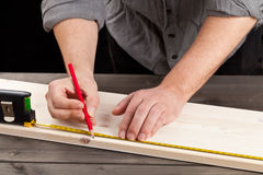 DIY. Young man measuring wooden plank - diy or home renovation concept stock images