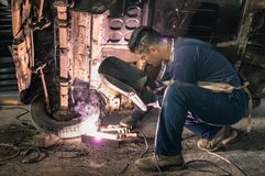 Young man mechanic worker repairing old vintage car body. In messy garage - Safety at work and protection wear - Guy with cool hair cut at vehicle renovation royalty free stock photography