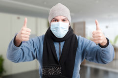 Young man with medical mask showing thumbup Stock Photo