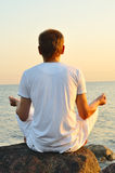 Young man is meditating. Young man is sitting on a stone and looking at sea sunrise. view from behind Stock Photo