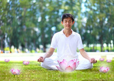 Young man meditating in autumn park. Stock Photography
