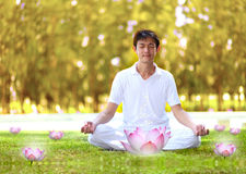 Young man meditating in autumn park. Royalty Free Stock Photography