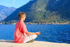 Young man meditating at the beach Royalty Free Stock Images