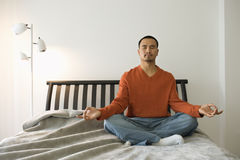 Young Man Meditating in Bedroom Stock Photo