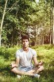 Young Man Meditating or Doing Outdoor Yoga Stock Photos