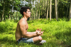 Young Man Meditating or Doing Outdoor Yoga Stock Images